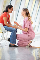 Female Nurse Offering Counselling To Depressed Woman