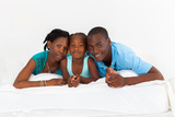 happy african american family lying on bed