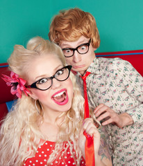Girl pulling a tie of her nerdy friend