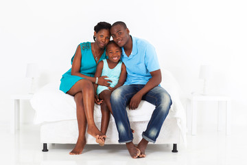 happy african family sitting on bed