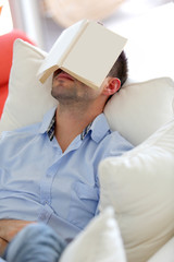 Young man sleeping in sofa with book covering his face
