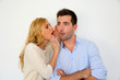 Girl whispering to boyfriend's ear on white background