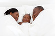 happy african american couple and baby boy sleeping