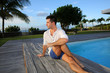 Young man doing stretching exercises on pool deck