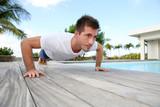 Young man doing pushups on pool deck