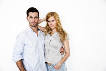 Trendy young couple standing on white background