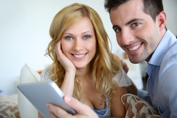 Cheerful couple websurfing with digital tablet at home