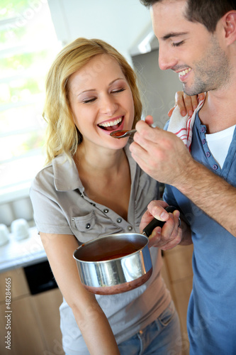 Woman tasting italian sauce cooked by boyfriend