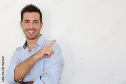Cheerful young man showing message on whiteboard