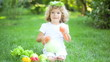 Happy child playing with fruits and vegetables in spring park