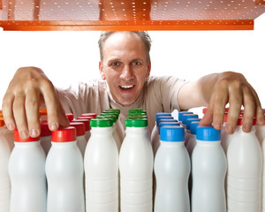The man selects dairy products in the shop