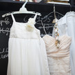 Wedding dress and suit hanging at a wall