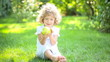 Happy child eating apple in spring park. healthy eating concept