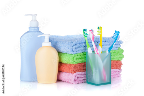 Four colorful toothbrushes, cosmetics bottles and towels