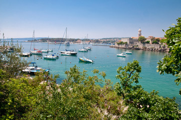 Boats on little port beside Krk old town view with vegetation -