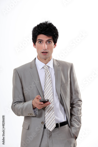Businessman in shock at his cellphone