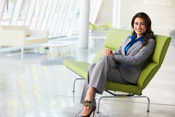 Portrait Of Businesswoman Sitting On Sofa In Modern Office