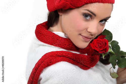 Brunette holding rose to face