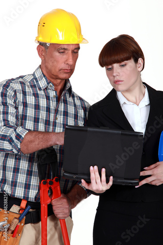Builder and architect using laptop together