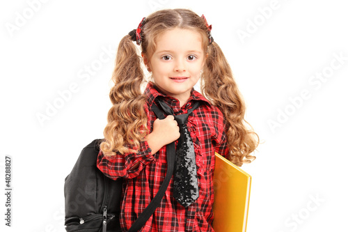 A little girl standing with backpack and book