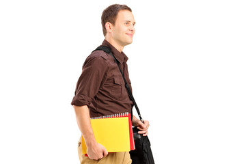 A male student with shoulder bag holding books and walking