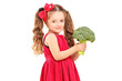 A smiling girl holding a broccoli