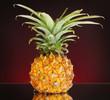 Ripe pineapple on dark red background