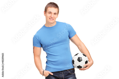 A young man leaning on a wall and holding a soccer ball