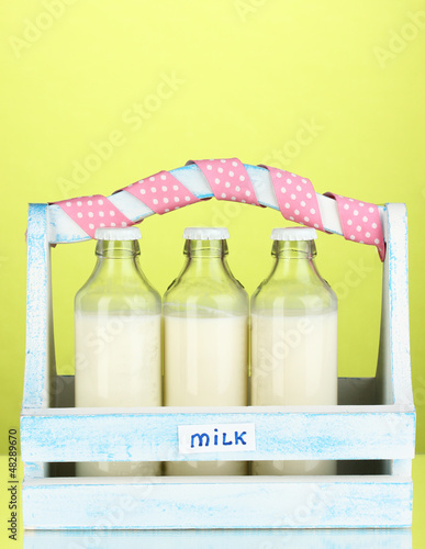 Milk in bottles in wooden box on green background