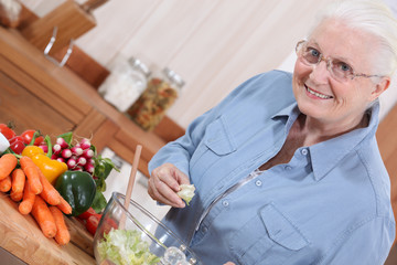 Old lady in kitchen preparing salad