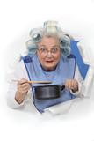 Elderly lady stirring sauce pan