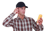Puzzled tradesman staring at his multimeter poster