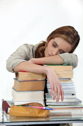 student sleeping over a pile of books