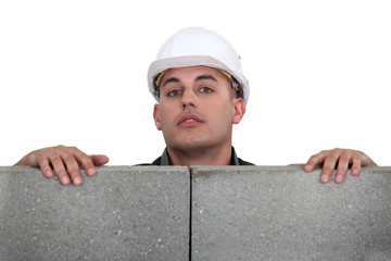 Builder looking over a block wall