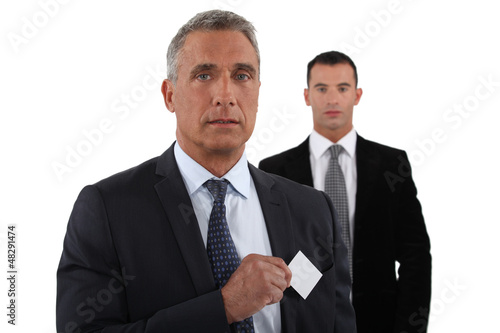 Company CEO removing business card from pocket