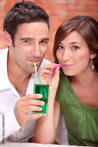 Couple drinking the same cocktail
