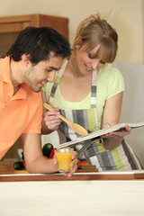 Couple with a recipe book in the kitchen