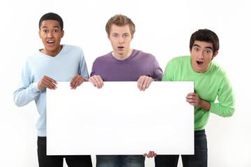 Three surprised men holding poster