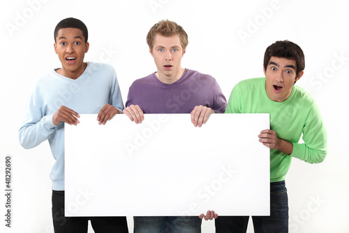 Three surprised men holding poster