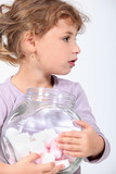 Little girl holding a jar full of marshmallows.