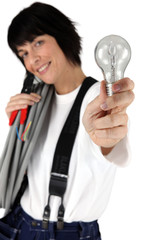 Female electrician showing light bulb