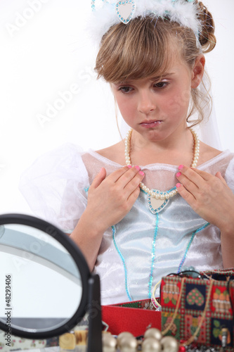 Girl dressed as a princess trying on necklace