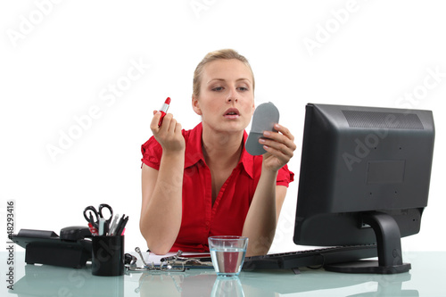 Blond woman applying lipstick in office
