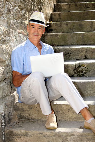 senior ma n relaxing outdoors with his laptop