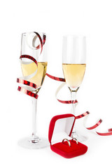 Two Valentine's champagne glasses with jewelery on white