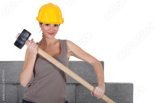 female bricklayer holding hammer