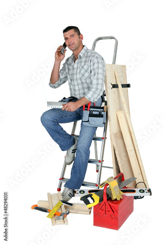 Laborer with phone and laptop sitting on a ladder