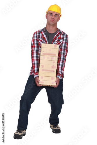 Tradesman carrying a heavy load of bricks
