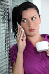 businesswoman talking on her cell and drinking her coffee