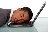 Young businessman asleep on laptop